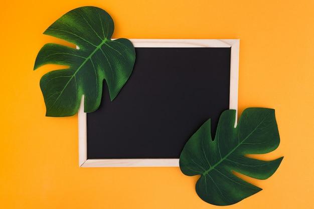 Cadre avec feuilles tropicales