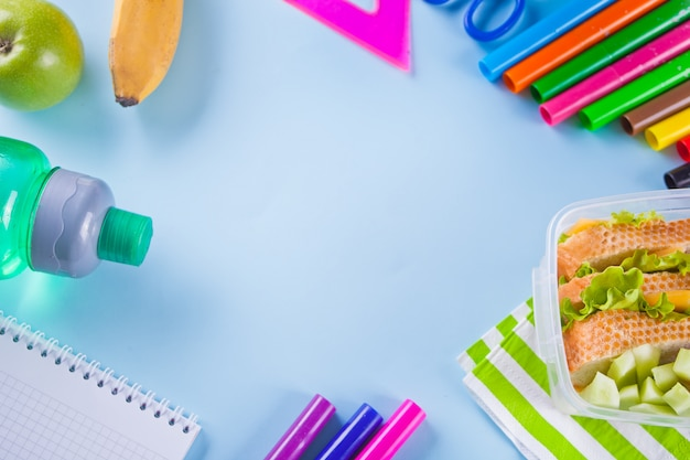 Cadre avec des feutres colorés, un cahier, une pomme verte, un sandwich sur bleu