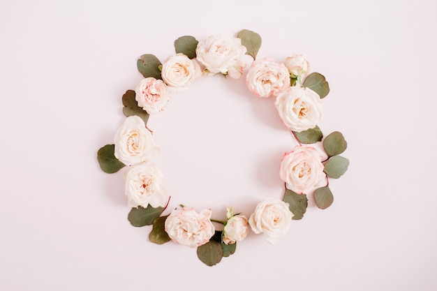 Cadre fleuri fait de roses beiges, branches d'eucalyptus sur fond rose pastel pâle. mise à plat, vue de dessus