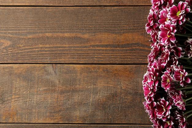 Cadre de fleurs d'automne de chrysanthèmes sur une table en bois marron avec une place pour une inscription. vue de dessus