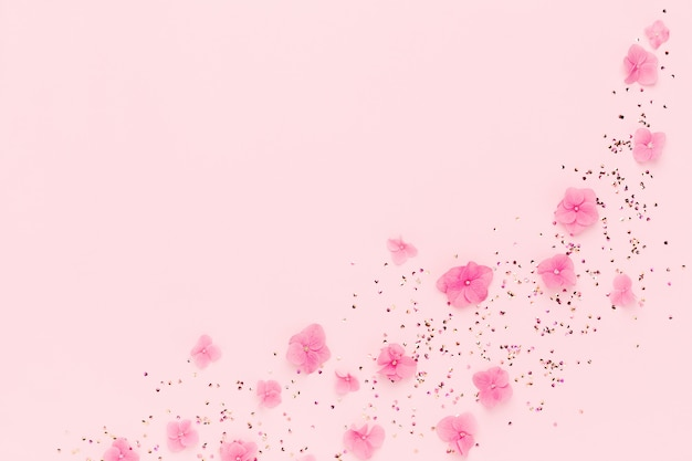 Cadre de fleurs et de confettis répartis sur rose.