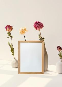 Cadre avec des fleurs contre un mur minimal blanc