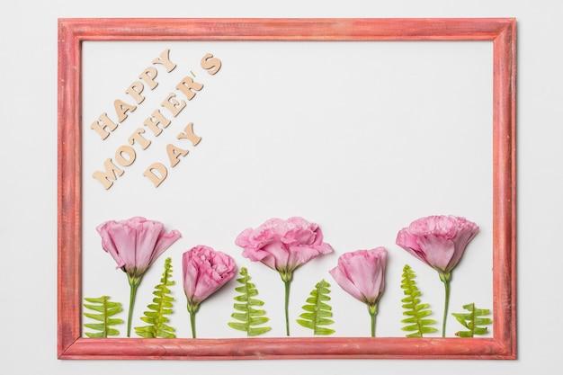 Cadre avec des fleurs fraîches et des plantes près du titre de la fête des mères heureux