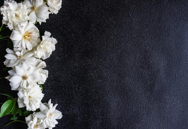 Cadre avec fleurs roses blanches sur pierre sombre avec espace copie