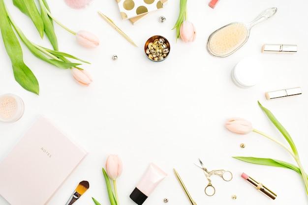 Cadre de fleurs de tulipes roses, accessoires et cosmétiques sur blanc