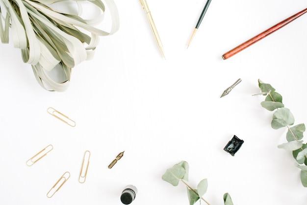 Cadre floral sur blanc avec stylo, pinceau, eucalyptus et clips