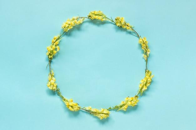 Cadre floral couronne ronde de fleurs jaunes sur fond bleu.