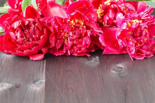 Cadre floral avec pivoines roses sur bois