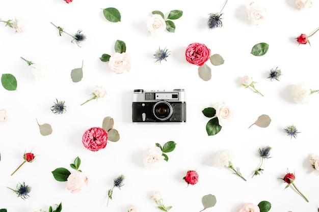 Cadre floral plat laïque avec appareil photo rétro vintage, motif de boutons de fleurs rose rouge et beige sur blanc