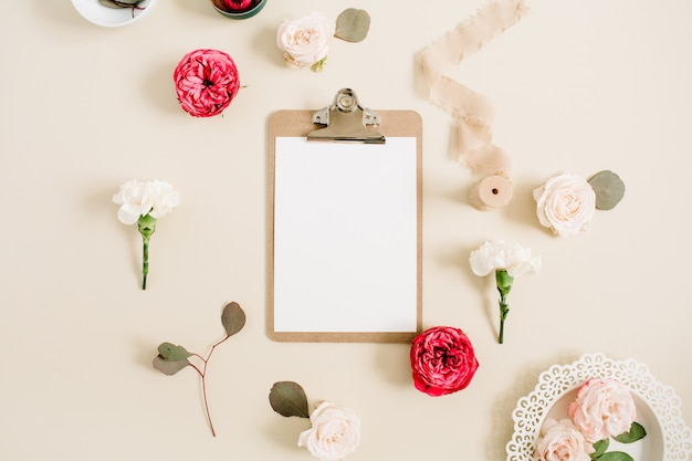 Cadre floral plat avec presse-papiers vierge, boutons de fleurs roses rouges et beiges, oeillet blanc, eucalyptus, ruban sur fond pastel beige pâle. vue de dessus