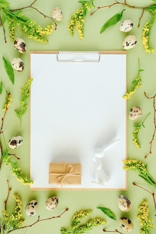 Cadre floral de printemps de pâques et papier vierge blanc. branches d'arbres naturels, fleurs jaunes, œufs de caille, bloc-notes de presse-papiers sur fond vert