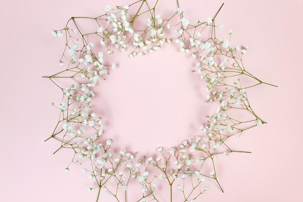 Cadre floral sur surface rose