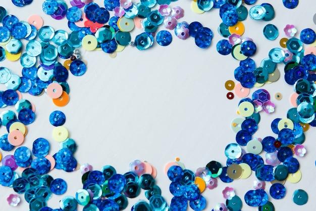 Cadre sur fond blanc de paillettes colorées et bleues