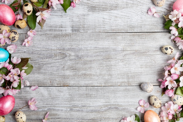 Cadre de fond de fleurs de pommier rose, oeufs de caille et oeufs de poule de pâques colorés