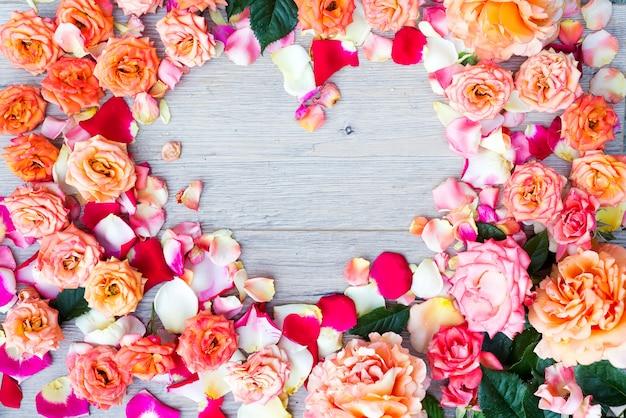 Cadre de forme de coeur fleurs rose sur fond en bois. lay plat, vue de dessus. fond de la saint-valentin.