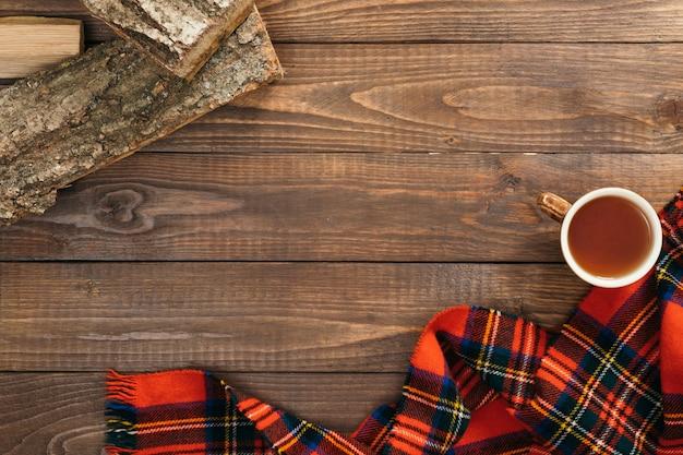 Cadre de foulard rouge féminin, tasse de thé, bois de chauffage sur fond en bois