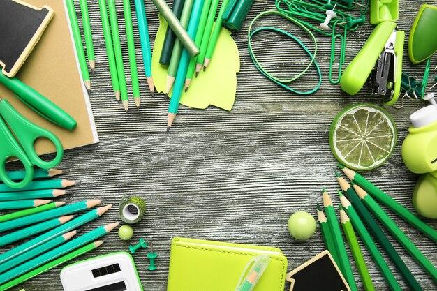 Cadre de fournitures de bureau vert sur une surface en bois grise