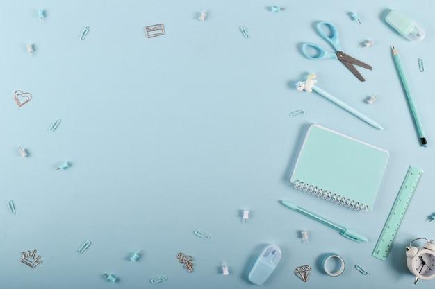 Un cadre de fournitures scolaires aux couleurs pastel sur fond bleu clair, espace pour le texte. mise à plat, vue de dessus, espace de copie.