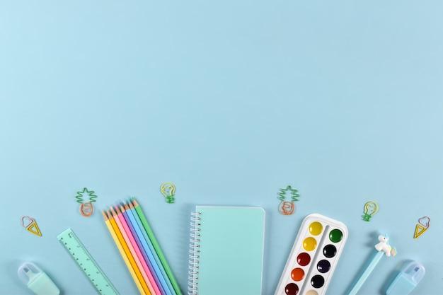 Un cadre de fournitures scolaires aux couleurs pastel sur fond bleu clair, espace pour le texte. retour à l'école. c'était plat.