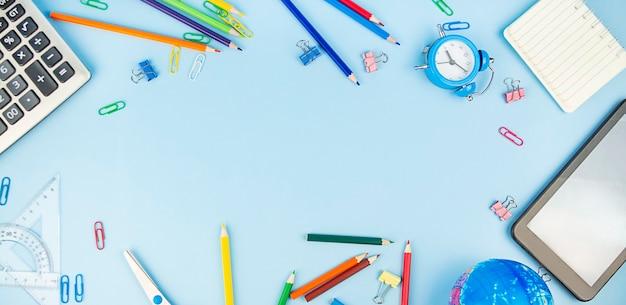 Cadre de fournitures scolaires sur un bleu