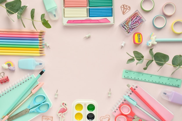 Un cadre de fournitures scolaires de couleur pastel sur fond rose, une place pour le texte. retour à l'école. fournitures de bureau. mise à plat, vue de dessus, espace de copie.