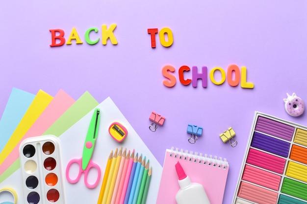 Un cadre de fournitures scolaires de couleur pastel sur fond violet, une place pour le texte. disposition plate, vue de dessus, un endroit pour copier. retour à l'école