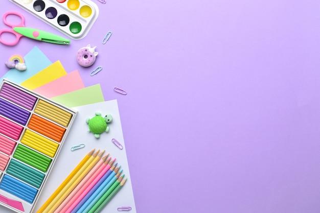 Un cadre de fournitures scolaires de couleur pastel sur fond violet, une place pour le texte. disposition plate, vue de dessus, un endroit pour copier.