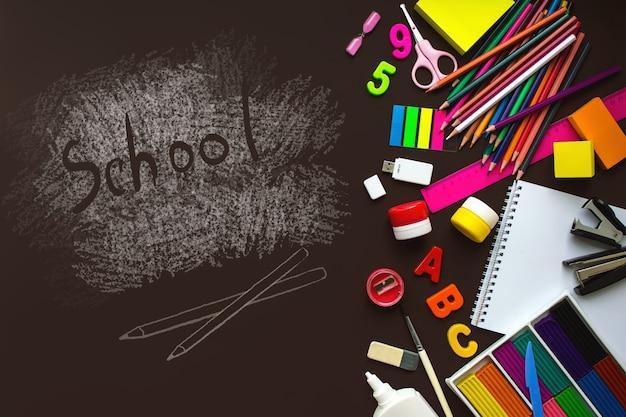 Cadre avec fournitures scolaires sur fond de tableau noir. vue de dessus. cadre de fournitures scolaires et de bureau.
