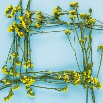 Cadre de frontière fait avec des fleurs jaunes sur fond bleu