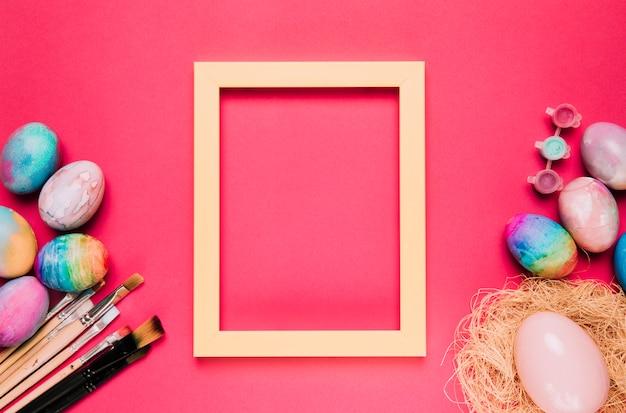 Un cadre de frontière jaune vide avec des oeufs de pâques colorés et des pinceaux sur fond rose
