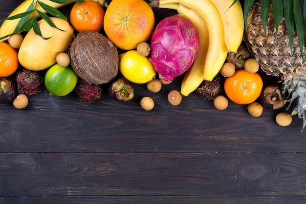 Cadre de fruits tropicaux arc-en-ciel en bonne santé avec des feuilles de palmier sur une table en bois bleue