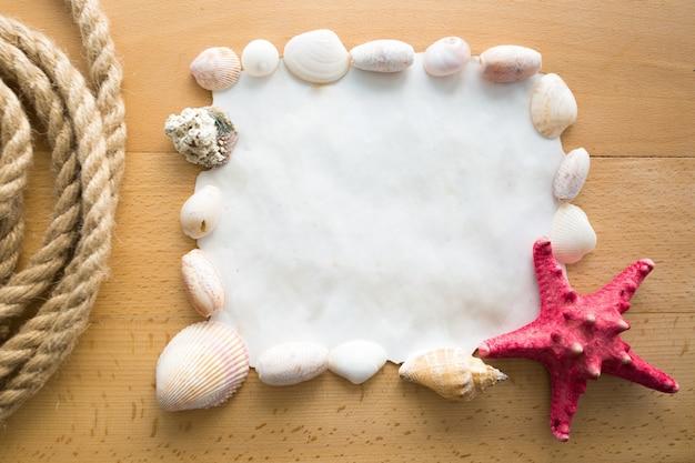 Cadre en gros plan avec espace de copie décoré de coquillages et d'étoiles de mer rouges