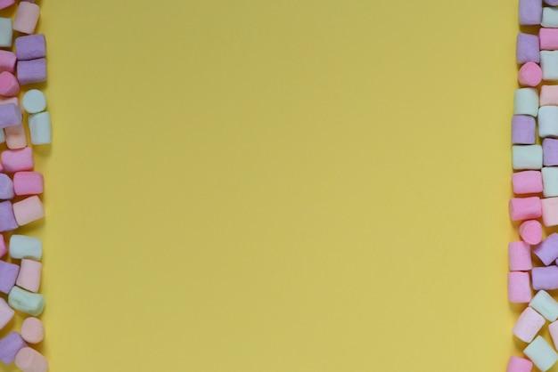 Cadre de guimauves multicolores sur fond jaune. bannière, carte postale.