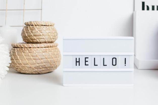 Cadre hello sur une table blanche avec des paniers en paille