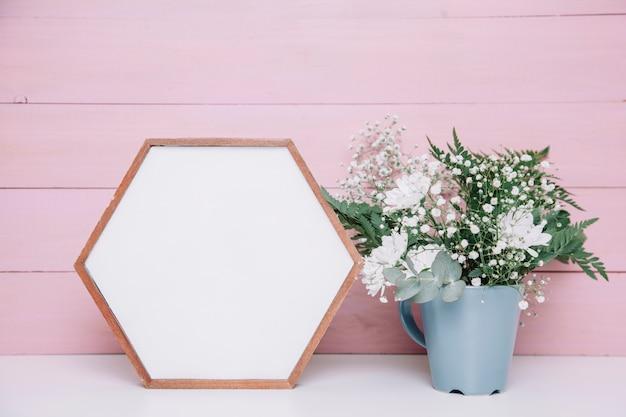 Cadre hexagonal à côté du pot de fleurs