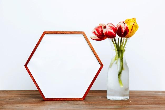 Cadre hexagone près de fleurs dans un vase