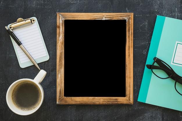 Cadre d'image vide; tasse à café et papeterie sur tableau noir