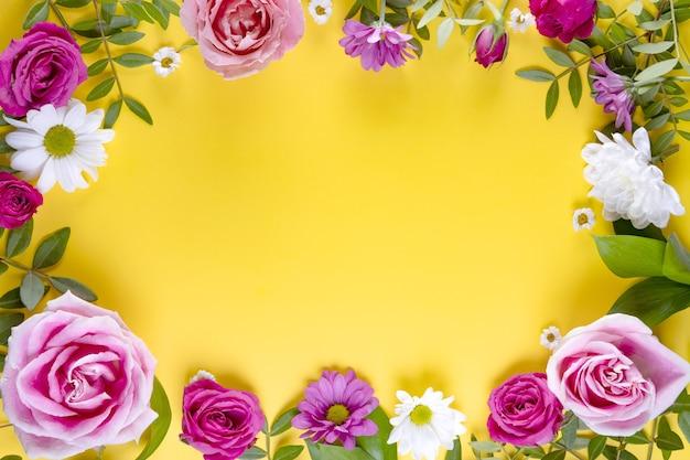 Cadre jaune d'été décoré de belles fleurs d'été avec un espace vide pour le texte des roses roses et