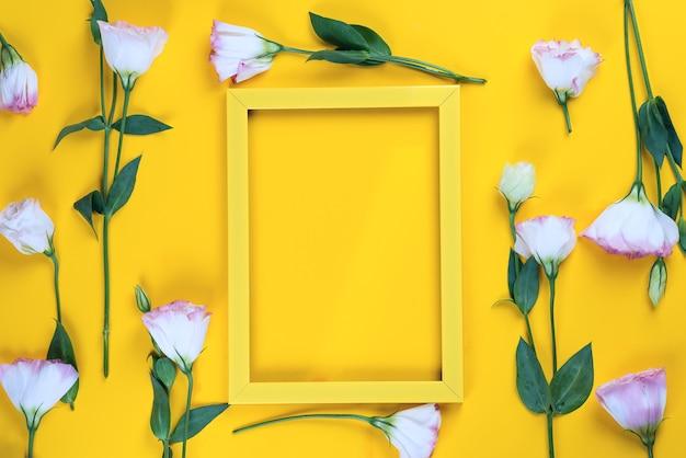 Cadre jaune vide et fleurs eustoma comme couche sur la surface du papier jaune