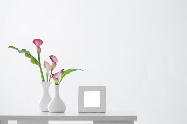 Cadre et lis calla rose dans un vase sur une surface blanche