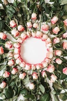 Cadre avec maquette d'espace copie vierge faite de fleurs roses roses sur blanc