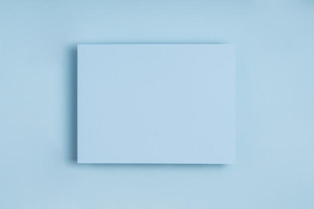 Cadre minimal de papier bleu sur fond pastel délicat.