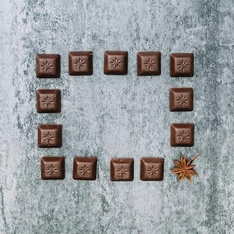Cadre de morceaux de chocolat avec un anis étoilé sur un vieux mur