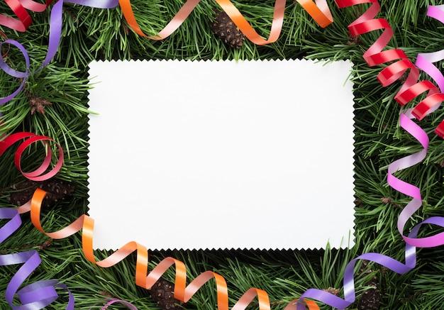 Cadre de noël avec des branches décorées de pin et une feuille de papier blanc. copiez l'espace pour le texte de vacances, de félicitations ou de publicité