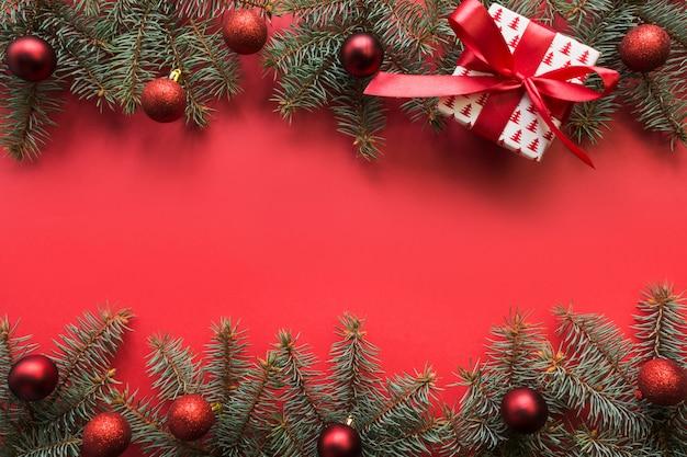 Cadre de noël avec des branches à feuilles persistantes, boules rouges, cadeau sur rouge