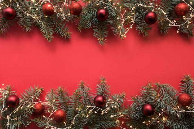 Cadre de noël avec des branches à feuilles persistantes, guirlande, boules rouges, cadeau sur rouge