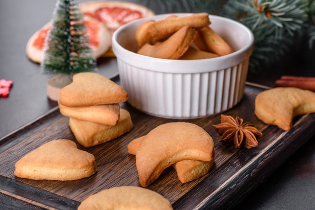 Cadre de noël avec des branches de sapin, des biscuits de pain d'épice, des épices, des anneaux d'orange séchés et des jouets de noël sur fond de pierre