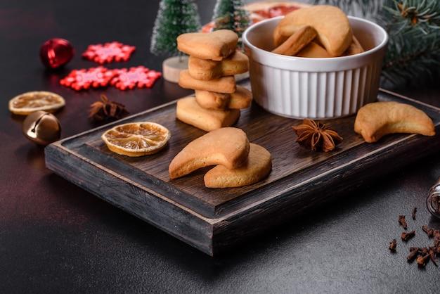 Cadre de noël avec des branches de sapin, des biscuits de pain d'épice, des épices et des anneaux d'orange séchés
