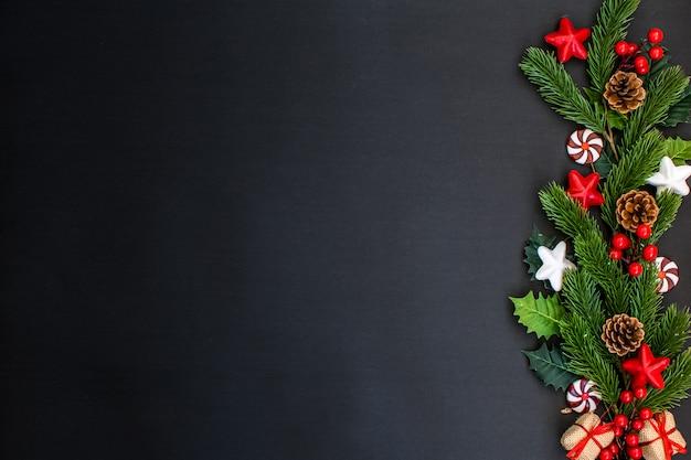 Cadre de noël avec des branches de sapin, des bonbons, des étoiles, des boîtes-cadeaux et des pommes de pin sur noir