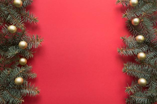 Cadre de noël avec des branches de sapin, des boules d'or sur rouge